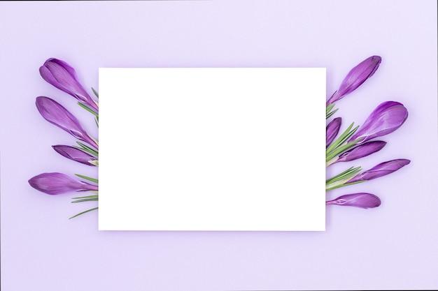 Vakantie achtergrond met geïsoleerde witte middendeel omgeven door paarse achtergrond en een boeket bloemen aan de zijkanten
