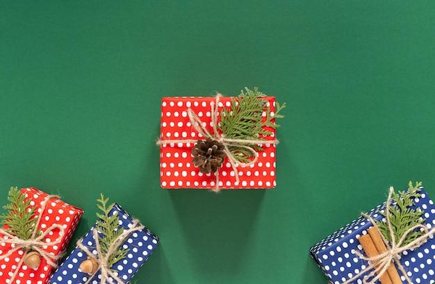 Vakantie achtergrond, rode en blauwe geschenkdozen in polka dots en thuja twijgen met kerstboom
