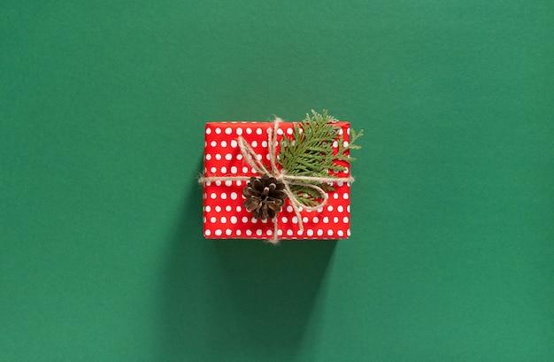 Vakantie achtergrond, rode geschenkdoos in polka dots en thuja twijgen met kerstboom kegel