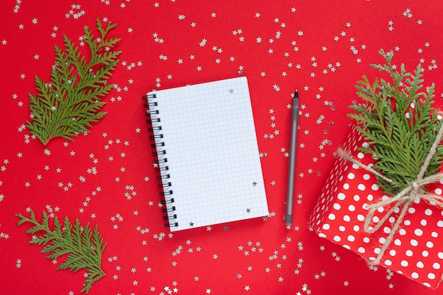 Vakantie achtergrond, rode geschenkdoos in polka dots met lint en boog en thuja twijgen op een rode achtergrond met glitter zilveren sterren, open spiraal kladblok en pen, plat lag, bovenaanzicht