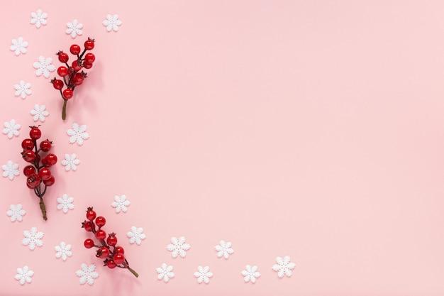 Vakantie achtergrond, twijgen van meidoorn op een roze achtergrond met sneeuwvlokken, plat lag, bovenaanzicht