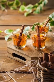 Vakantie, alcohol drinken, drank, digestief concept. geschoten met sterke alcohol en kaneelstokje op een houten tafel