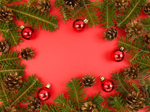 Vakantie ansichtkaart met fir tree takken, kegels en rode kerstballen op een rode achtergrond. kerst plat lag met kopie ruimte.