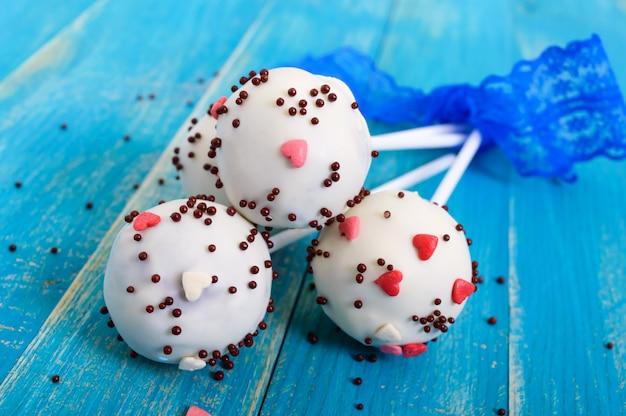 Vakantie behandelt. cake pops. koekjes taarten in witte chocolade glazuur op een heldere blauwe houten achtergrond.