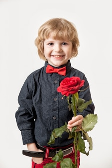 Vakantie cadeau. bloemen van een kleine heer. rood nam in de handen van een jongen op een witte achtergrond toe