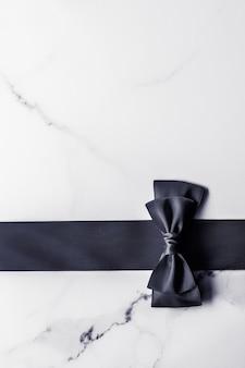 Vakantie cadeau decoratie en verkoop promotie concept zwart zijden lint en strik op marmeren achtergrond flatlay