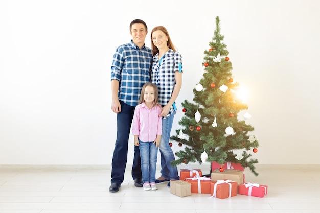 Vakantie, cadeaus en kerstboomconcept - klein gezin heeft gelukkige tijd samen met kerstmis