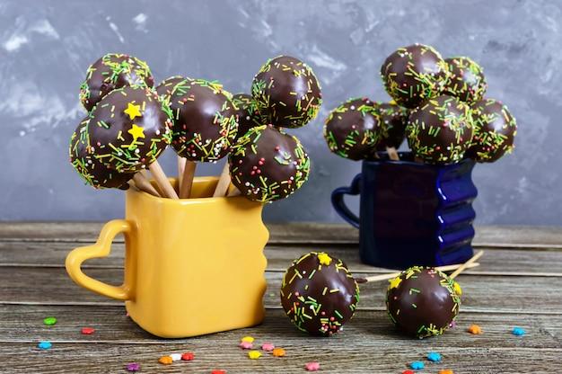 Vakantie cake springt, versierd met witte en zwarte chocolade in kopjes op een houten achtergrond. snoep op een stokje.