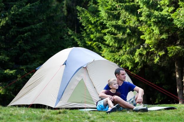 Vakantie camping. vader en zoon nemen rust in de buurt van tent na wandelen in het bos reizen en buitenshuis activiteiten. gelukkige familierelaties en een gezonde levensstijl.