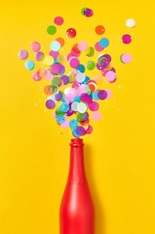 Vakantie champagne rood geschilderde fles met veelkleurige glitter als een schuim van bubbels op een gele achtergrond, kopieer ruimte. plat leggen.