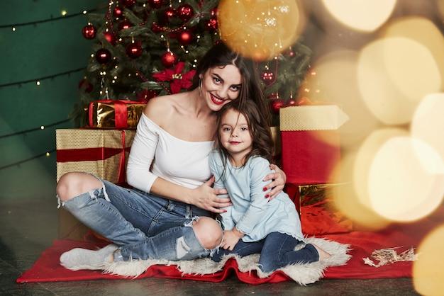 Vakantie conceptie. vrolijke moeder en dochter zitten in de buurt van de kerstboom die erachter