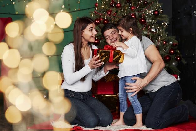 Vakantie delen met dochter. leuke familie zit in de buurt van de kerstboom met geschenkdozen op winteravond, genietend van de tijd samen doorbrengen