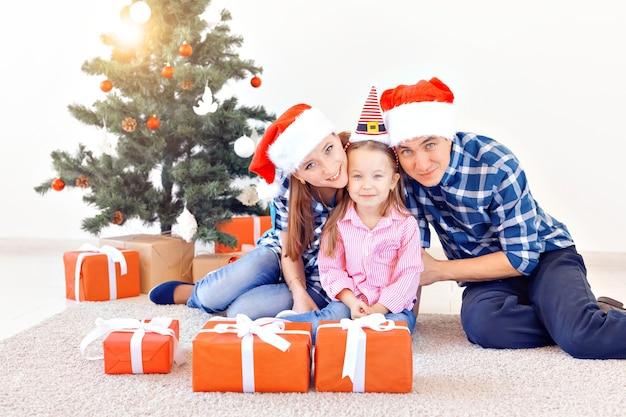 Vakantie en feestelijk concept - gelukkig familieportret door kerstboom.