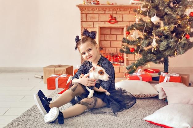 Vakantie en jeugdconcept - portret van een klein gelukkig schattig kindmeisje en puppy met kerstcadeau.