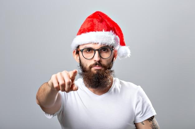 Vakantie en mensen concept - portret van een knappe brutale man in kerstmuts. over grijze achtergrond.