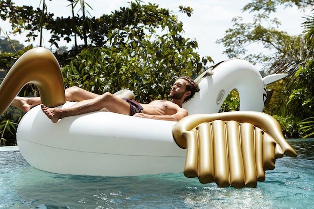 Vakantie en ontspanning concept. jonge blanke man met fit lichaam ontspannen op opblaasbare matras in de vorm van een draak