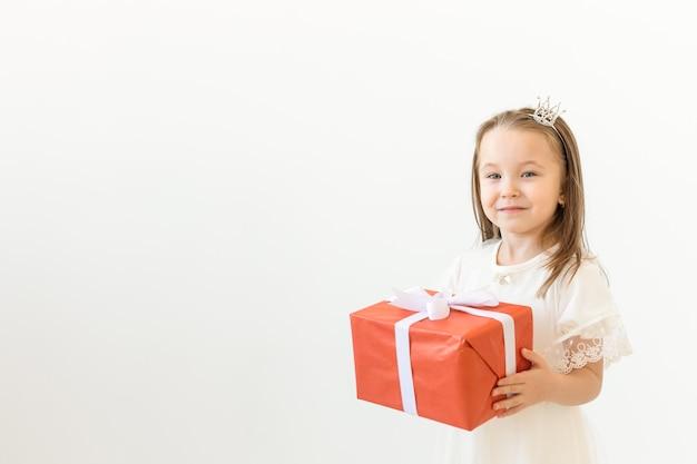 Vakantie en presenteert concept. kleine meisje glimlach en rode geschenkdoos op wit te houden