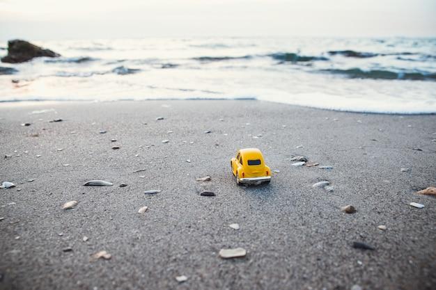 Vakantie en reizen concept. gele stuk speelgoed auto op het strand in het zonlicht in de zomer