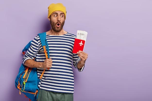Vakantie en reizen concept. verrast ongeschoren man poseert met rugzak op schouders