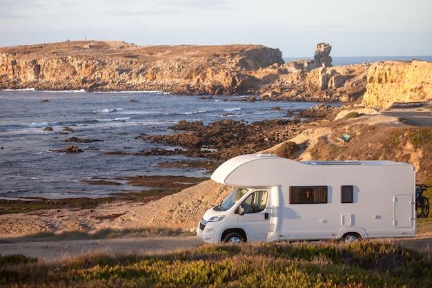 Vakantie en reizen in caravan. camper van camper op kustweg met een zonsondergang