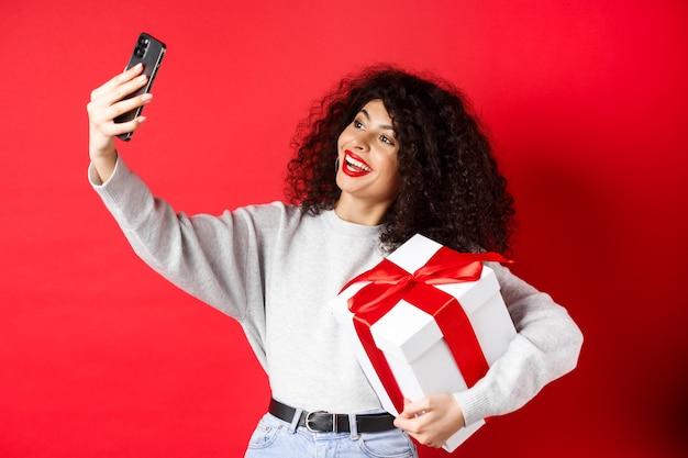 Vakantie en tech concept. gelukkige vrouw die selfie neemt met haar cadeau, cadeau en smartphone vasthoudt, staande op rode achtergrond