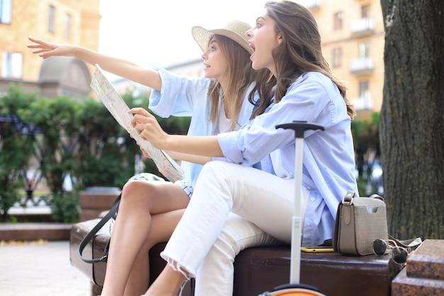 Vakantie en toerisme concept - mooie meisjes op zoek naar richting in de stad.