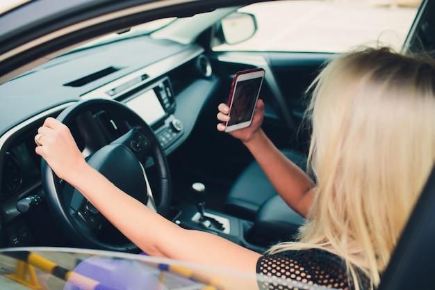 Vakantie en toerismeconcept - glimlachende tiener die selfie beeld met smartphonecamera in openlucht in auto nemen.