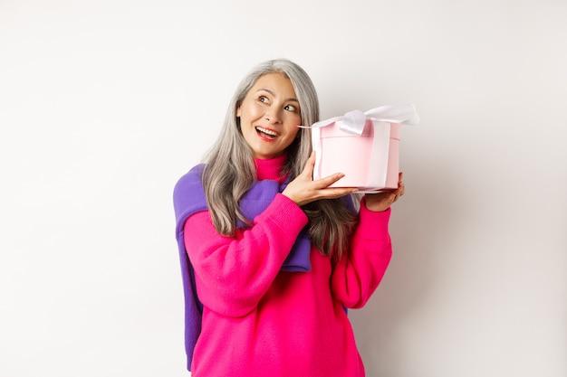 Vakantie en valentijnsdag concept. gelukkige aziatische rijpe vrouw die doos met cadeau schudt, raden wat er in zit, staande op een witte achtergrond.