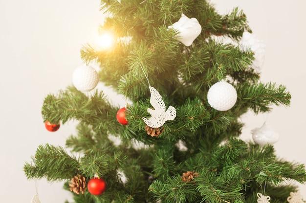 Vakantie en viering concept - close-up van versierde kerstboom op witte background