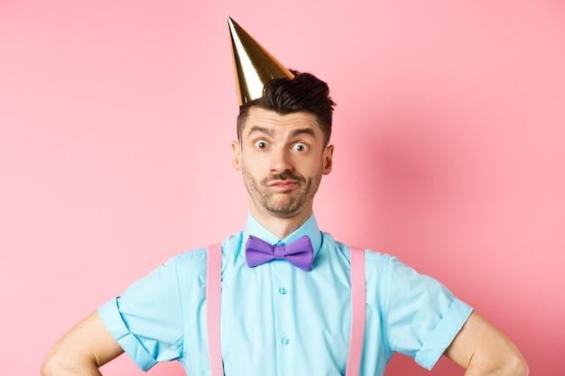 Vakantie en viering concept. close-up van verwarde mannelijke entertainer in feestmuts en vlinderdas, op zoek verbaasd en geschokt, staande over roze achtergrond.