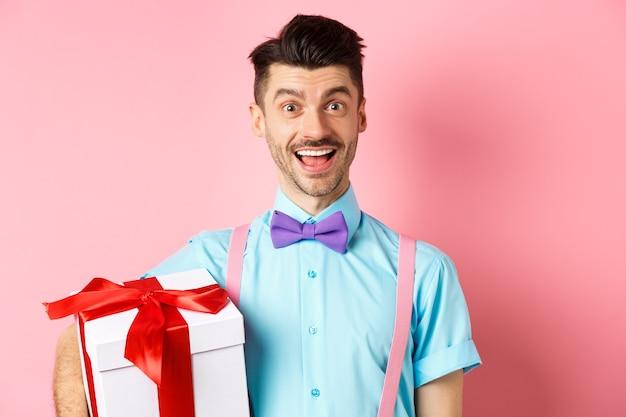 Vakantie en viering concept. gelukkig jonge man in feestelijke outfit met grote huidige doos voor verjaardag, vrolijk en glimlachend, roze achtergrond staan.