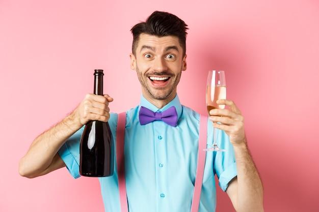 Vakantie en viering concept. gelukkig jonge man plezier, fles champagne en glas tonen, toast maken op gebeurtenis, glimlachen en kijken naar camera, roze achtergrond.