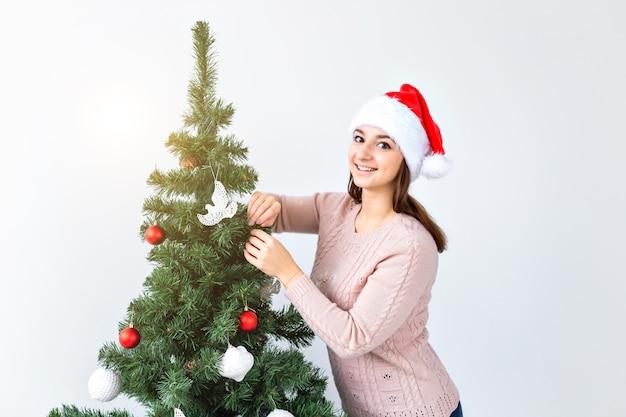 Vakantie en viering concept - gelukkige brunette vrouw in santa's hoed versiert een kerstboom thuis in de woonkamer.