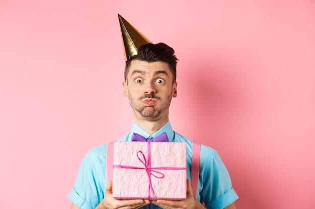 Vakantie en viering concept. grappige kerel staren camera verbaasd, feestmuts dragen, verjaardagscadeau houden en adem inhouden, pruilen naar camera, roze achtergrond.