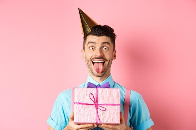 Vakantie en viering concept. grappige kerel viert verjaardag, draagt een feestmuts, houdt b-dag cadeau en toont tong met blij gezicht, roze achtergrond.