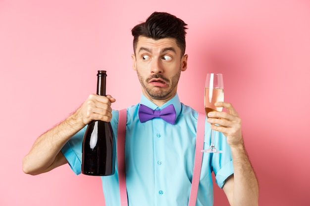 Vakantie en viering concept. verward dronken man kijken naar lege fles champagne, glas vasthouden, drinken op feestje, staande over roze achtergrond.