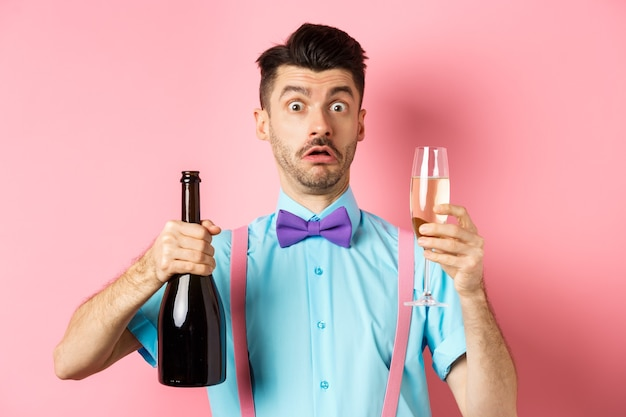 Vakantie en viering concept. verwarde man staarde geschrokken naar de camera terwijl hij een glas champagne schonk, staande verbaasd over roze achtergrond.