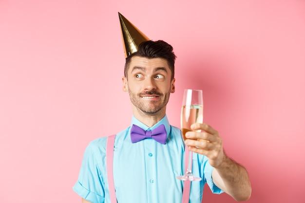 Vakantie en viering concept. vrolijke jongeman viert verjaardag in feestmuts, denken aan spraak, glas chamapgne verhogen voor toast, roze achtergrond.