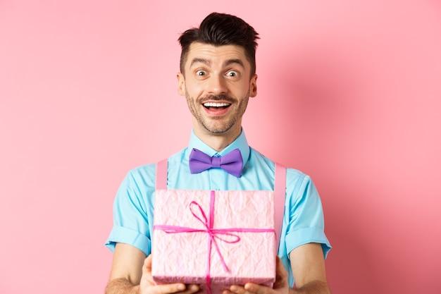 Vakantie en viering concept. vrolijke kerel wenst gelukkige verjaardag en geeft u cadeau verpakt in doos, staande over roze achtergrond in feestelijke kleding.