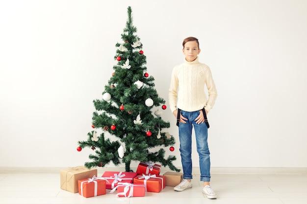 Vakantie en winter jeugd concept - lachende tiener jongen permanent in de buurt van kerstboom op witte achtergrond.