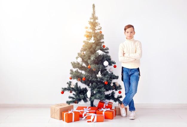 Vakantie en winter jeugd concept - lachende tiener jongen permanent in de buurt van kerstboom op witte achtergrond. Premium Foto