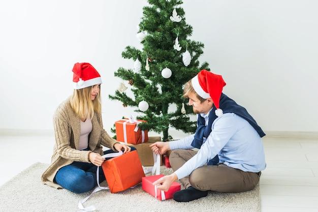 Vakantie, familie en feestelijk concept - koppel met kerstcadeaus thuis.