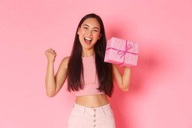 Vakantie, feest en lifestyle concept. triomfantelijk gelukkig aziatisch schattig feestvarken dat vrolijk kijkt, houdt van het ontvangen van geschenken, het verhogen van de vuistpomp en het tonen van ingepakt cadeau, staande roze achtergrond.