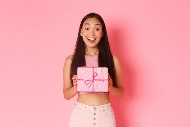 Vakantie, feest en lifestyle concept. vrolijk aziatisch meisje viert verjaardag ontvangt ingepakt cadeau, vraag me af wat er in het heden zit, geamuseerd over roze muur