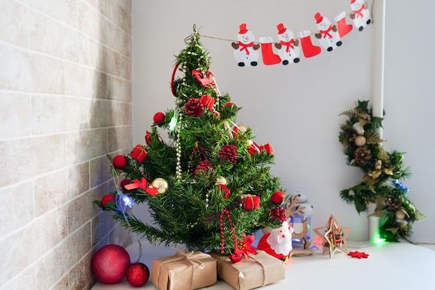 Vakantie, feest en thuis concept - keukentafel met kerstboom en papier presenteert
