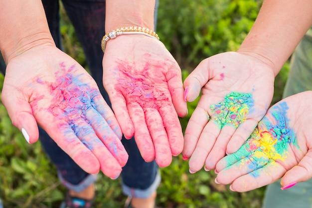 Vakantie, festival holi en familieconcept - palmen van jonge mensen bedekt met verschillende kleuren over de natuur