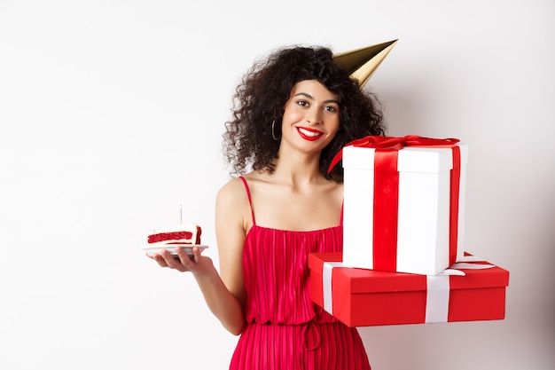 Vakantie. gelukkig elegante vrouw in feestmuts en rode jurk, met verjaardagstaart en geschenken, vieren b-dag, staande op witte achtergrond.