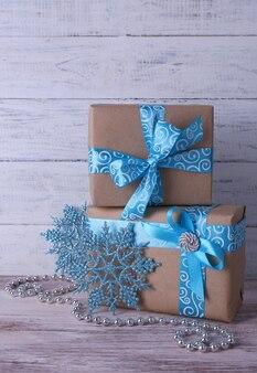 Vakantie geschenkdozen versierd met blauw lint op tafel op houten muur achtergrond