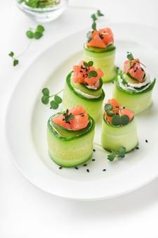 Vakantie groente voorgerechten. komkommersrolletjes met zachte kaas, stukjes gezouten zalm, microgreens en zwarte sesam geserveerd op een witte plaat. selectieve aandacht.