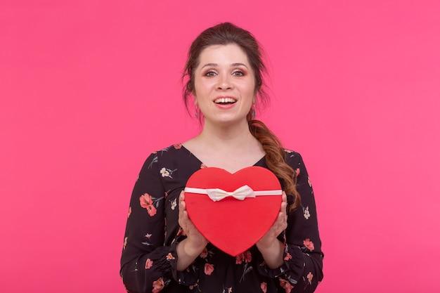 Vakantie, heden en verrassingsconcept - schoonheids gelukkig meisje met valentine giftdoos op roze